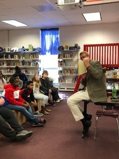 Mr. Blaine reads to fourth grade students