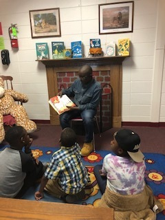 5th grade student reading Dr. Seuss to 1st graders