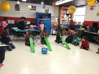 2nd Grade students are measuring how far their team cars roll at different heights.
