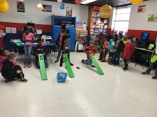 2nd Grade students measure how far their team cars roll from different heights.