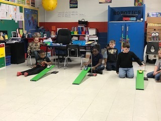 1st Grade Students measure how far their team car rolls from different heights.