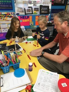 Mr. Snyder and second grade students are working on an experiment recreating the movement of the knee with straws and play dough.