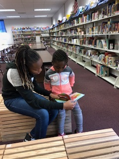 Older students are helping younger students read in the library!